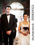 Small photo of Bride and groom standing at alter in church during religious wedding ceremony.