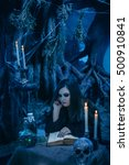 Small photo of On eve of Halloween witch casts a spell, uttering a terrible spell over ancient of arcane recipes.Fabulous, spooky voodoo shack.Candles, assorted bottles of potion.Fabulous concept.Fashionable toning