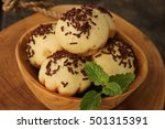 Small photo of Kue Cubit. Indonesian version of Dutch poffertjes; topped with chocolate sprinkles. Arranged on an artistic wooden bowl garnished with mint leaves. Placed on a wooden block.