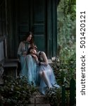 Small photo of Two luxury brunette with long hair in vintage dresses, sitting on threshold of old house in front of massive door.One lady put my head on my knees other.Fantastic shooting.Fashionable toning.Creative.