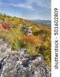 Small photo of Fall foliage colors the cliff edge at Bear Rocks in the Dolly Sods Wilderness in the Allegheny Mountains of West Virginia.
