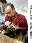 Small photo of Lecce, Italy - September 15, 2015: Sandro Riso, seen here painting a figurine, helps keep Lecce, Italy's tradition of papier-mâché sculptures alive at his shop, La Cartapesta.
