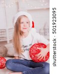 Small photo of Little smiling girl wearing Santa hat and festive dress sitting on the lambskin carpet.
