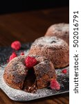 Small photo of Chocolate fondant cake with raspberries on dark background. Shallow focus