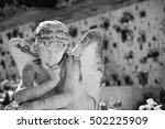 Small photo of Cemetery angel mourning for soul - All Souls' Day (with a blurred cemetery background - copy space)