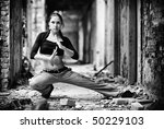 Young woman in a ruined building. Black and white contrast colors. - stock photo