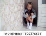 Small photo of Little aggrieved girl sitting in the corner of the room