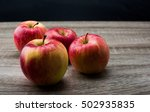 Four Apples On Wooden Table...
