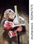 Small photo of Two whole garlic bulbs beside cloves on old wooden table for theme about pungent herbs for cooking and health