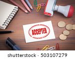 Small photo of Accepted stamp. Wooden office desk with stationery, money and a note pad