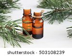Small photo of Dark glass bottles with pure aroma oil. Green Pine branches. Natural remedy.