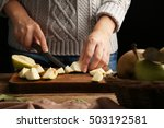 woman slicing pear on wooden
