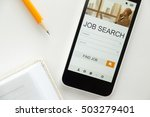 Small photo of Top view of a mobile phone lying on a white office desk, job search on the screen, part of a notebook, sharp pencils. Business concept