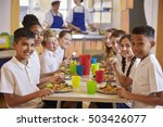 Stock photo kids at a table in a primary school cafeteria look to camera 503426077