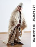 Small photo of young boy in traditional albanian clothing looking sideways with sheepskin mantle