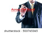 Small photo of Businessman hand writing Across The Board on a transparent wipe board.