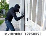 Burglar trying to force a door lock using a crowbar - stock photo