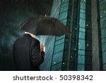 Businessman is walking toward a corporate building, holding an umbrella. Hard rain falling. - stock photo