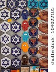 Small photo of Krakow, Poland - September 7, 2016: Souvenir magnets with jewish symbols (Magen David, menorah, hamsa) displayed for sale in jewish district Kazimierz, Krakow, Poland.
