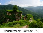 Small photo of Amazing nature view of green mountain forest and lonely tree growing on a rock with sky as a background. Outdoor natural landscape perspective. Caucasus, great nature forest landscapes of Russia