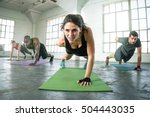 Small photo of Strong powerful intense fit female leader of athletic fitness team exercising one arm push ups