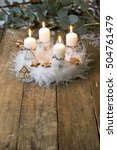 Small photo of white advent wreath with decoration, four candles burning