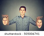 Small photo of Smiling man holding two different face emotion masks