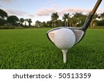 golf ball on tee with driver at  florida tropical course at dawn - stock photo