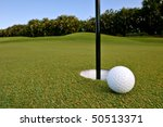 golf ball near pin and cup of green of florida tropical course - stock photo