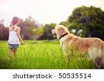 Stock photo young girl with golden retriever walking away into sun 50535514