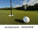 golf ball near pin and cup of green of florida tropical course, focus on ball - stock photo