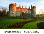 Kilkenny Castle in the evening. It is one of the most visited tourist sites in Ireland. Castle grounds with green lawn and flowers. Landmark in small town of Ireland