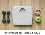 Stock photo weight scale healthy snack measuring tape and dumbbells on a table weight loss and sports 505757311
