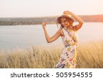 Beauty young girl outdoors enjoying nature. Fashion young woman in floral dress and stylish hat in meadow with copy space