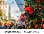 Small photo of Colorful Street with Christmas Decorations and Christmas tree with many people all around it.