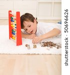 Little boy counting his savings laying on the floor with a pile of coins and an abacus - stock photo