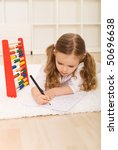 Little girl doing simple math exercises laying on the floor with an abacus - stock photo