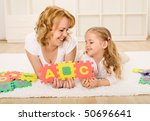 Woman and little girl having fun playing with alphabet puzzle on the floor - stock photo