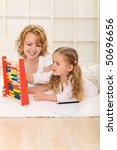 Woman and little girl learning math together laying on the floor - stock photo