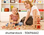 Little girl and woman playing on the floor with wooden blocks, building - stock photo