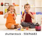 Kids painting their hands at home sitting on the floor - stock photo