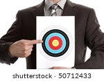 Businessman holding a target and pointing at the bullseye, copy space above for heading - stock photo