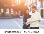 Small photo of Fashionably dressed couple of travelers lost in the streets of the old town. The hot young guy and his beautiful brunette opened the map exploring it to continue their romantic walk on a spring city