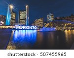 Stock photo nathan phillips square in toronto at night with the fountain the big writing and the old city 507455965