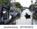 Small photo of A lone fisherman poles a flatboat along a canal in Lafitte, Louisiana, lined with shrimp boats.