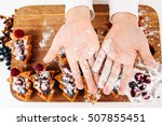 Small photo of Kid show palms in sugar powder flat lay. Top view on child hands above board with berry cakes, free space for text. Homemade bakery, children culinary, pastry making concept