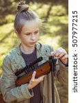 Small photo of Young girl shooting from the air rifle in the forest