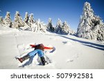 Young Woman Laying On Snow And...