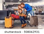Small photo of Packed and prepared for take-off. Smiling happy family doing holiday trip and looking map on digital tablet at airport hall