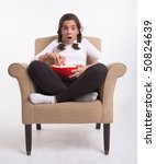 Girl sitting on an armchair with a popcorn bowl looking open-mouthed - stock photo